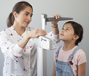 Healthcare provider measuring girl's height.